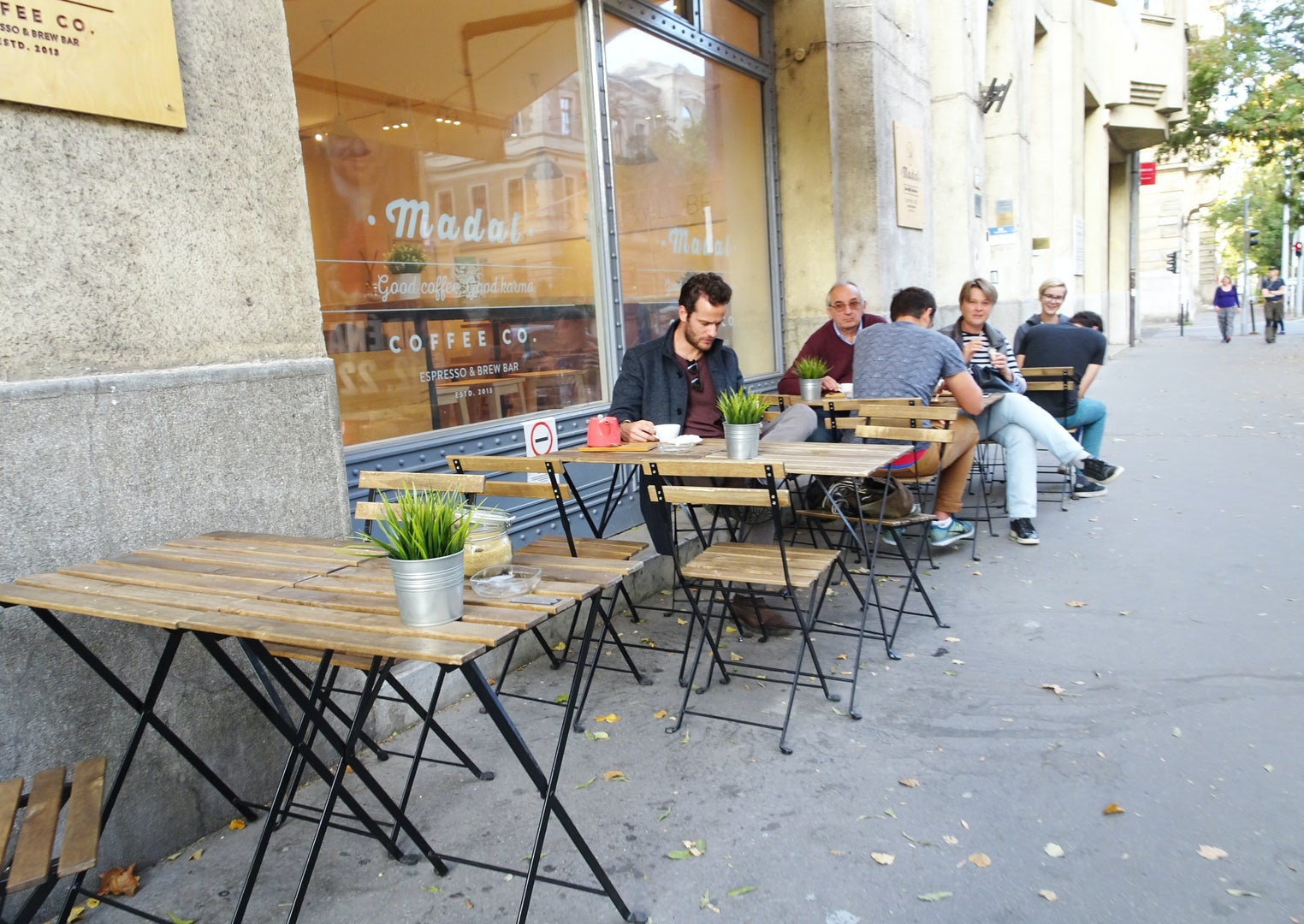 people seated outside Madal bar