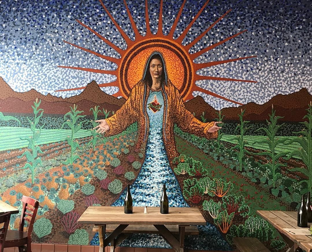 restaurant interior and wall painting of a saint at Gracias Madre