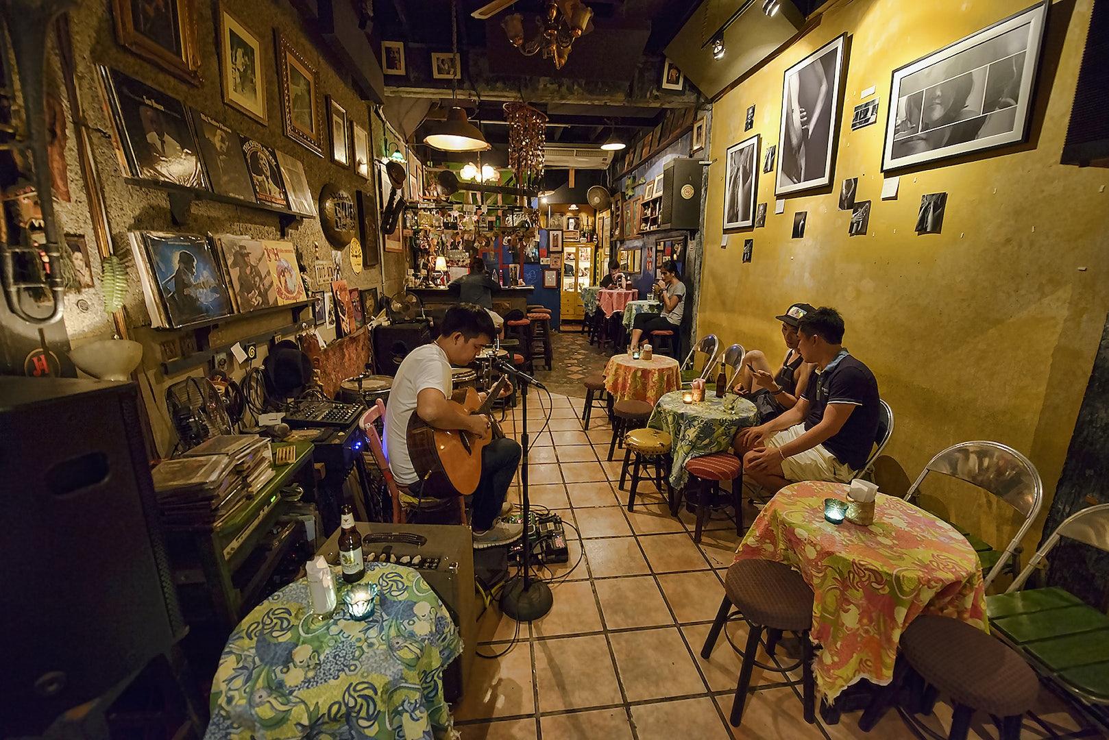 man playing guitar at Adhere the 13th Blues bar