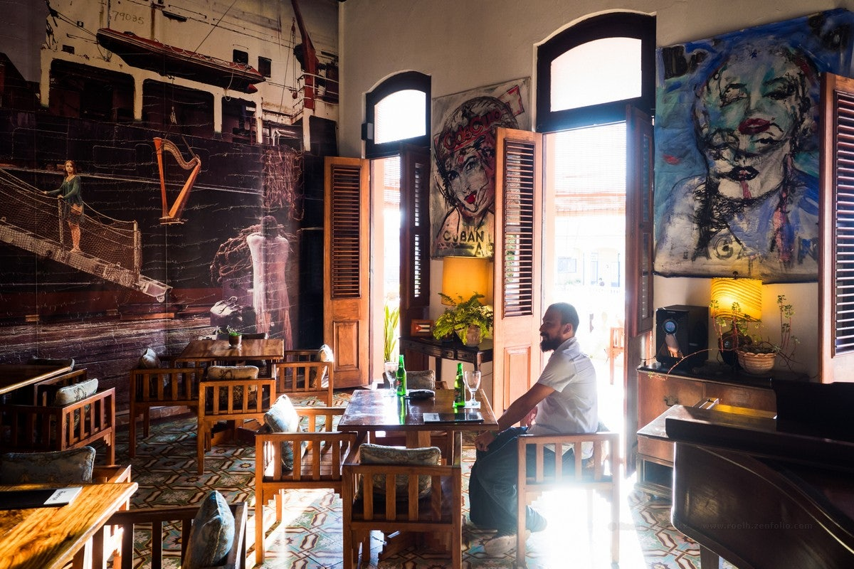 man sitting insde of Bar Madrigal in Havana