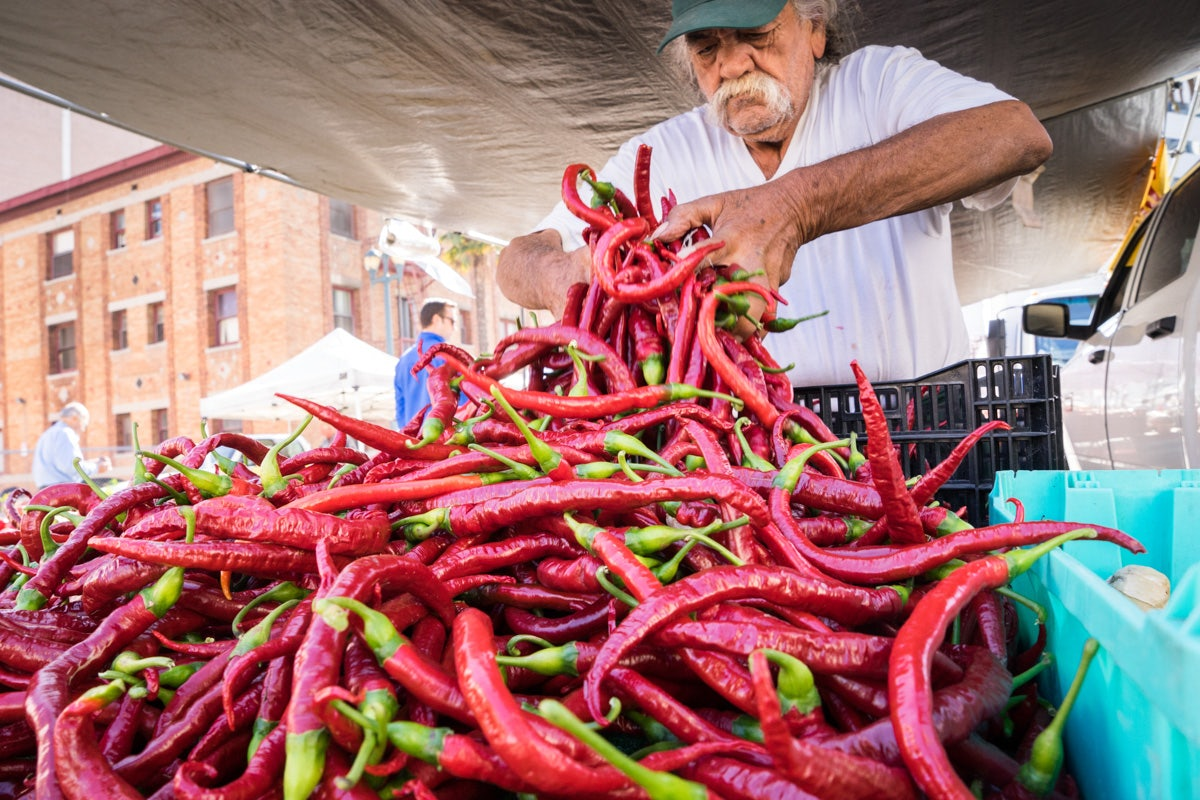 a man displaying chilli peppers the Farmers Market in Santa Monica