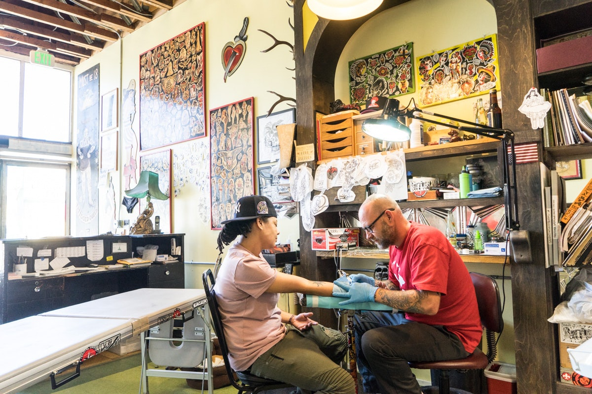 a man getting tattooed at the American Electric Tattoo Company