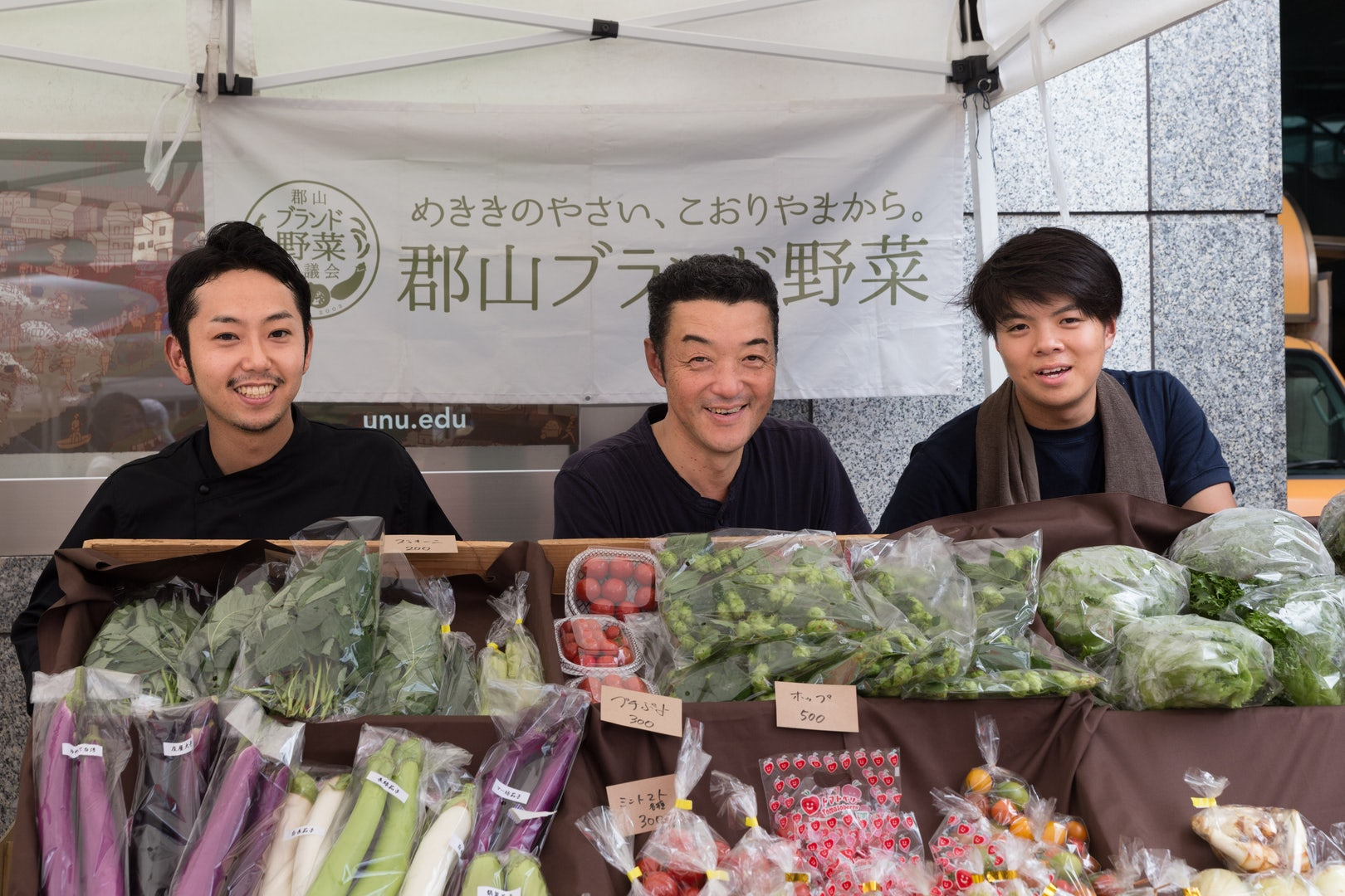 three Japanese men at a vegetable stand
