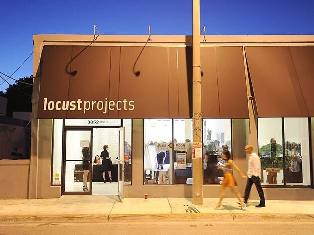 couple walking in front of Locust Projects store