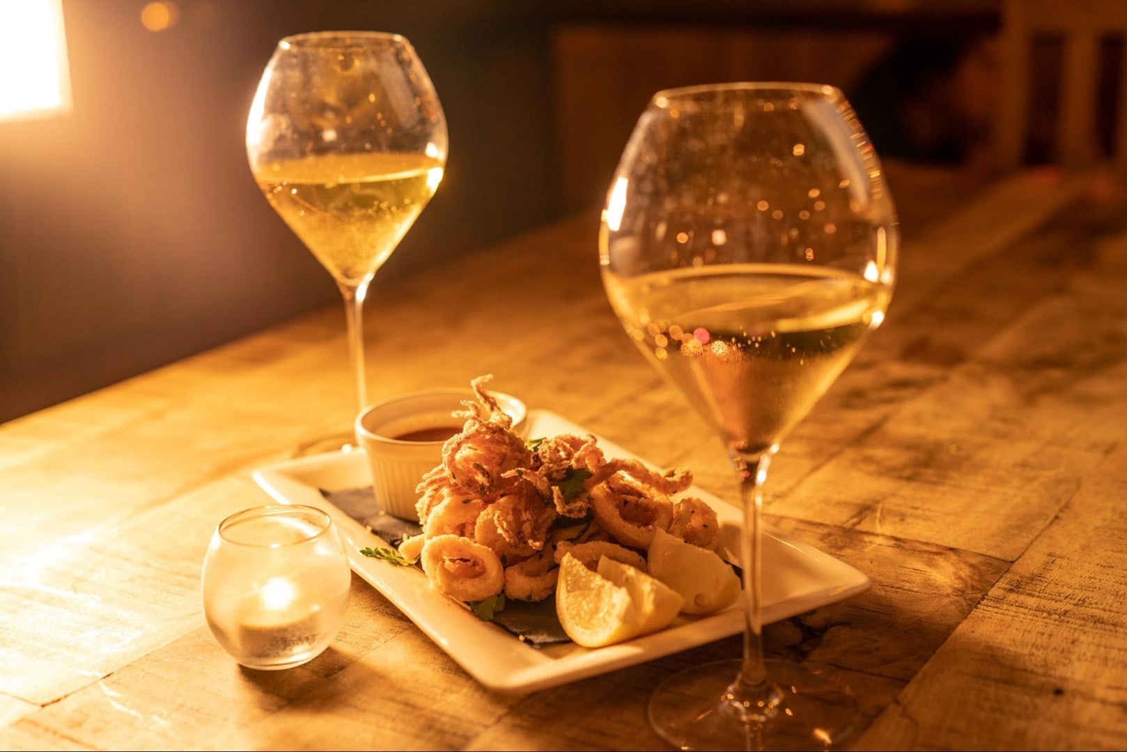 two glasses of white wine and fried baby squid at Via Verdi Miami