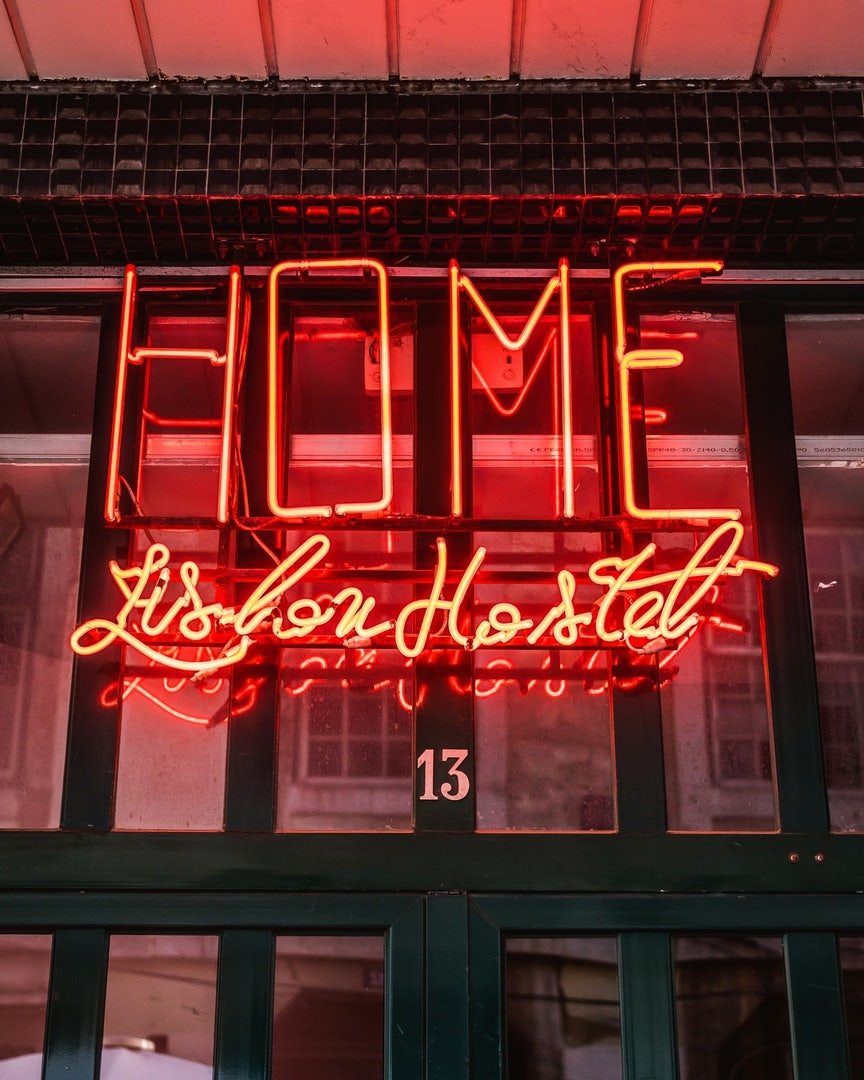 red neon sign of the Home hostel in Lisbon