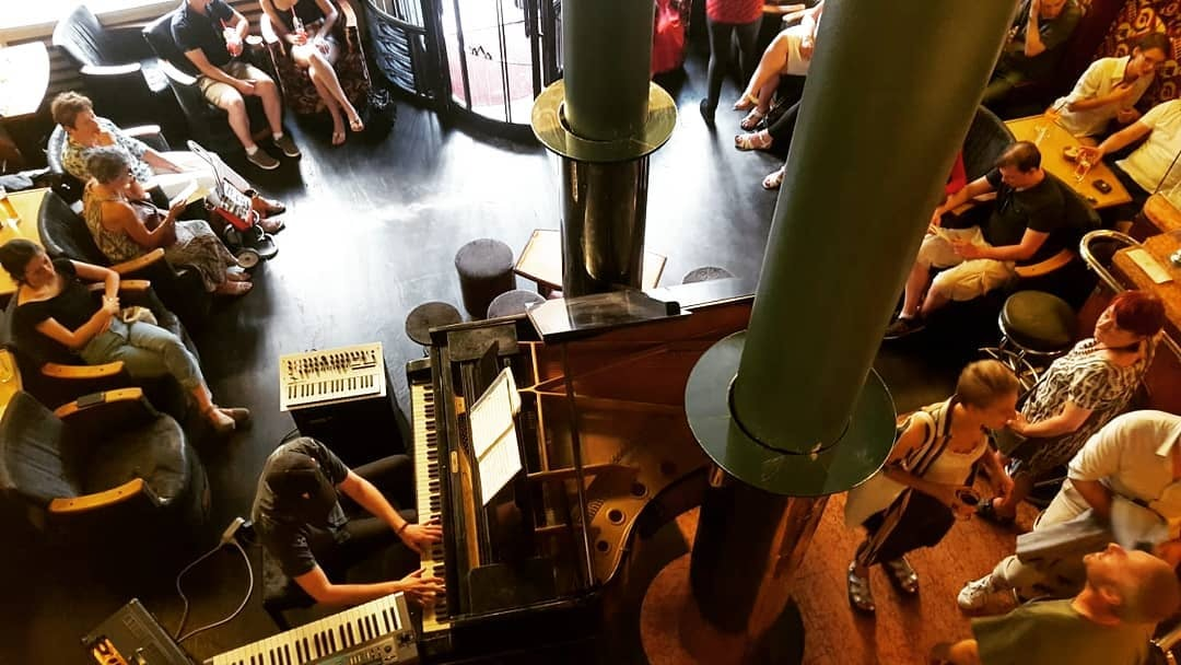a man playing piano at L'Archiduc cafe