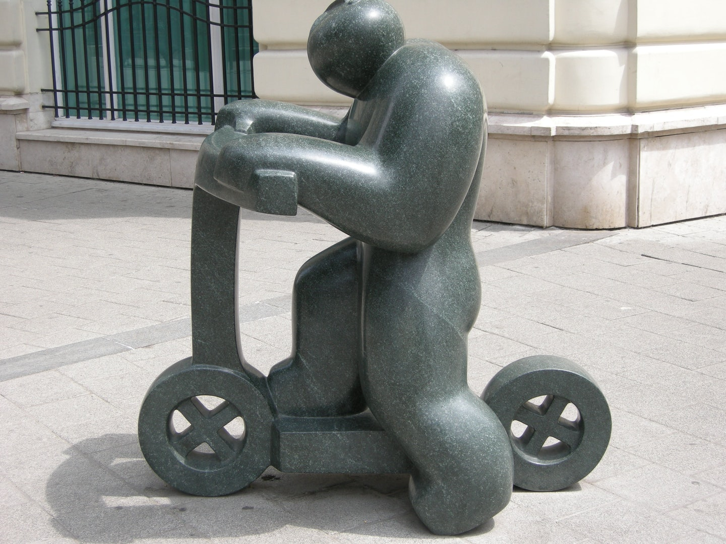 granite statue of a boy on a scooter