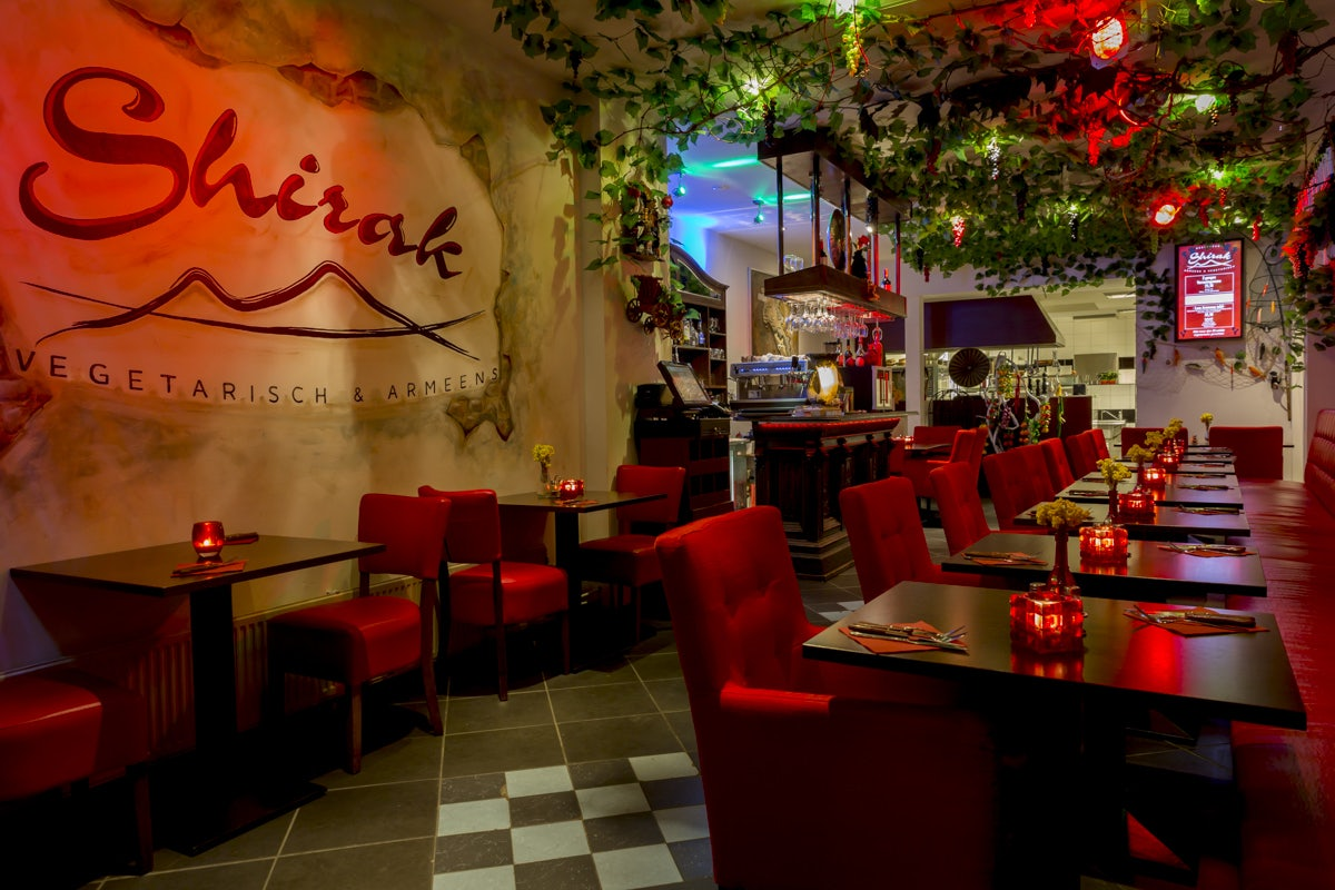 a red and dimly lighted interior of Shirak restaurant
