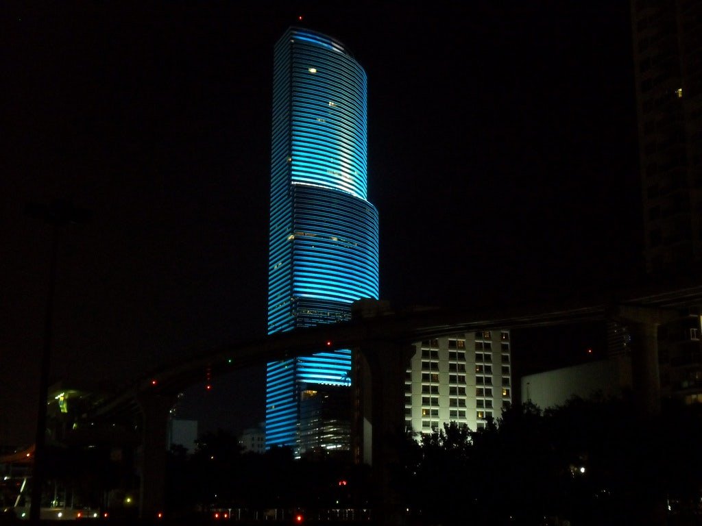 a blue lighted Miami Tower by night
