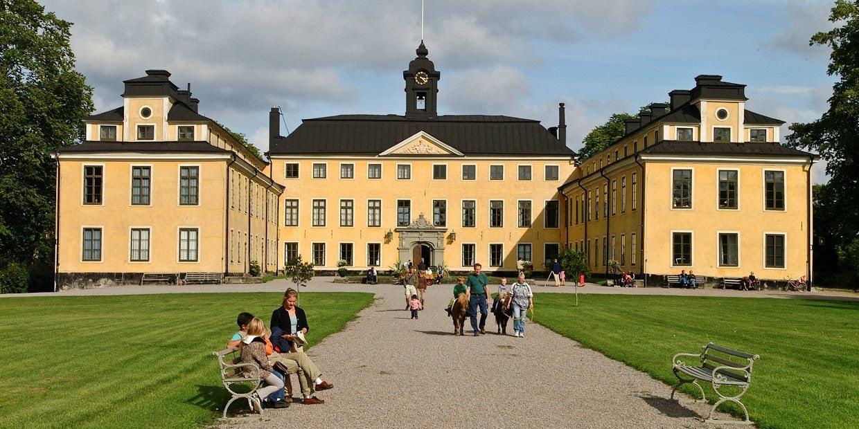 yellow exterior of the Ulriksdals Slott and people