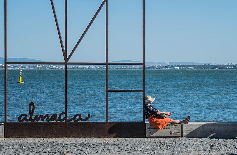 woman resting by the water at Ribeira das Naus
