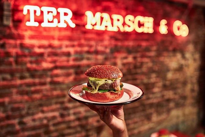 a burger on a plate and a neon sign of Ter Marsch & Co