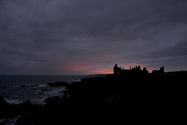 New Slains Castle in Scotland against a purple pink sky