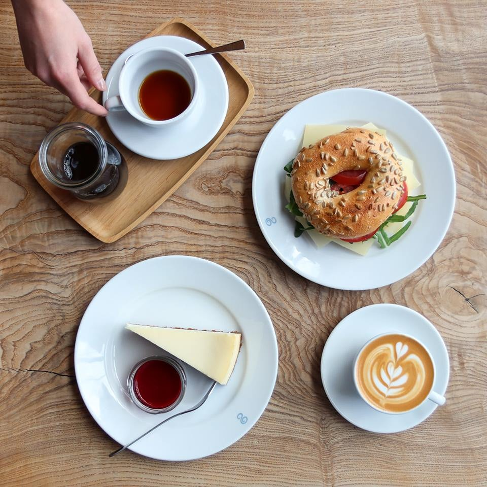 a cup of coffee and a bagel and cheesecake from Elbgold Hamburg