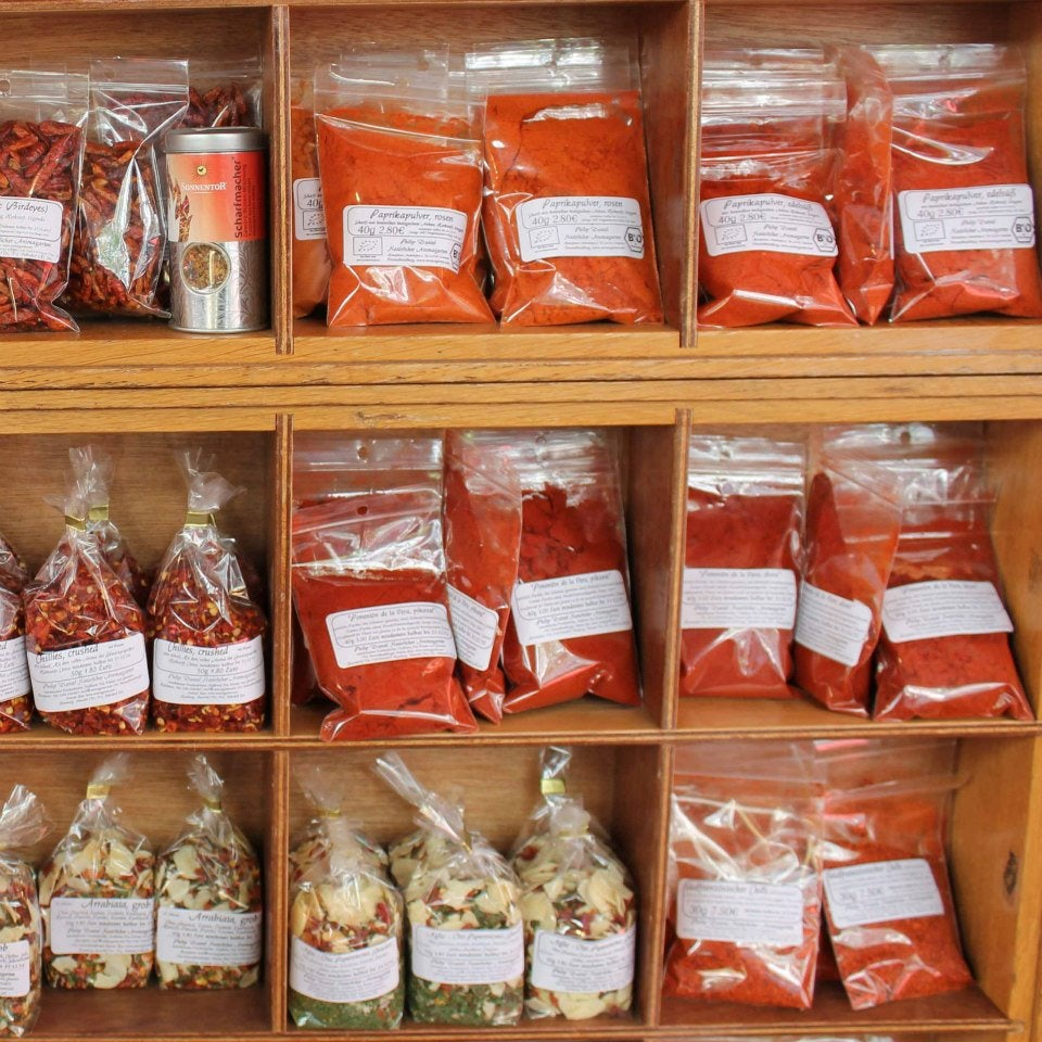a shelf full of red and orange coloured bags with spices