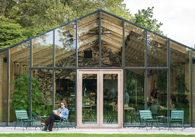 a woman sitting in front of Greens greenhouse bar