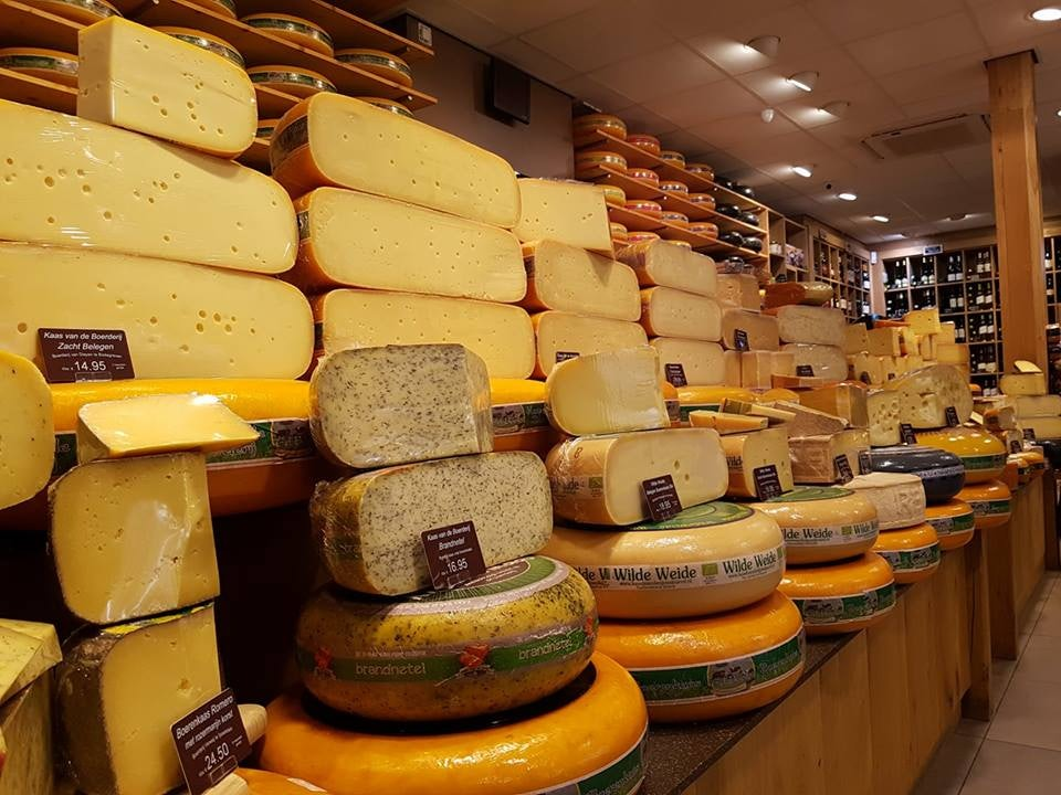 a wall stacked with rolls of cheese at Ed Boele store