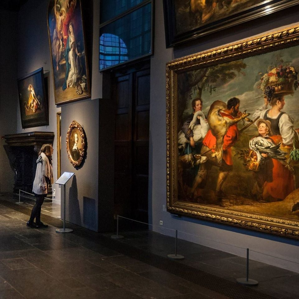 a woman admiring paintings at the Rubenshuis museum in Antwerp