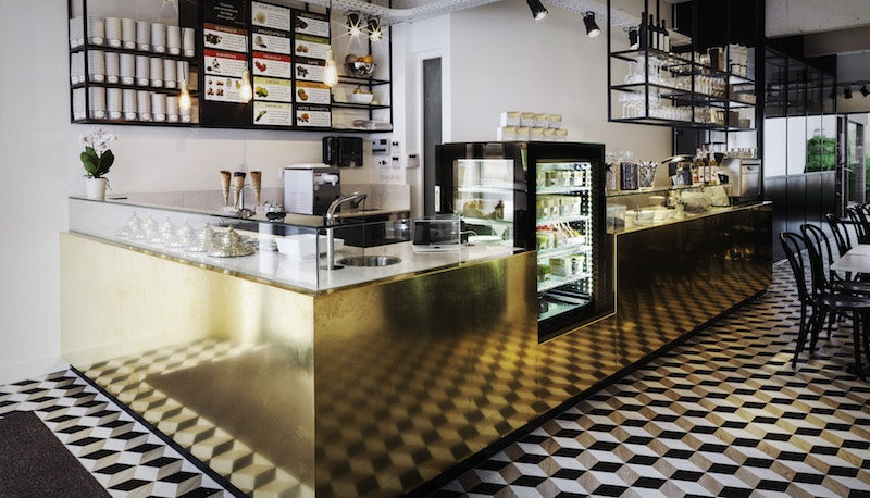 Cremerie Germaine interior with optical tiles and golden counter