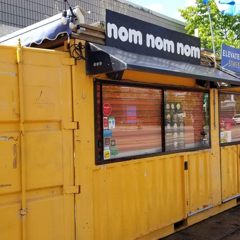 yellow exterior of Nom Nom Nom Poutine bar