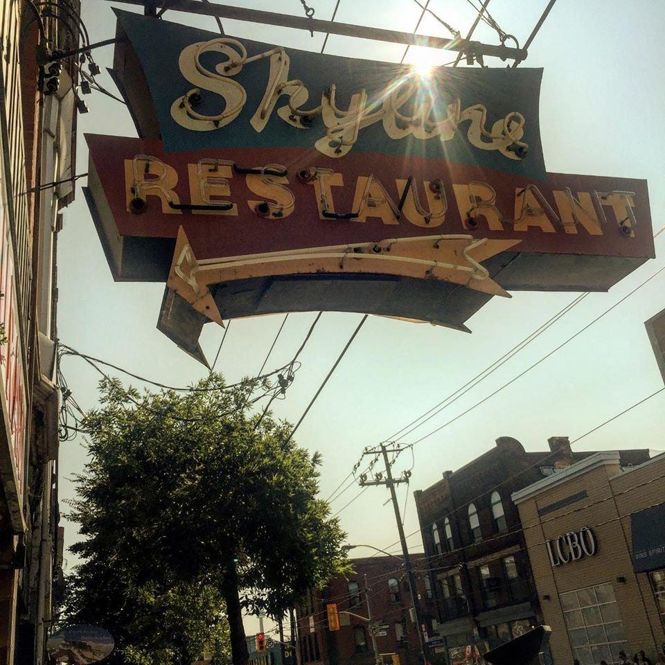 street sign of Skyline Restaurant with arrow