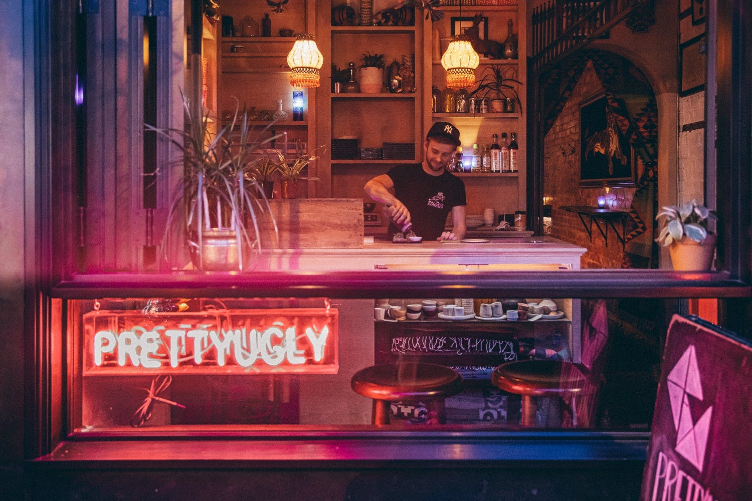 bartender serving a cocktail at Pretty Ugly Bar