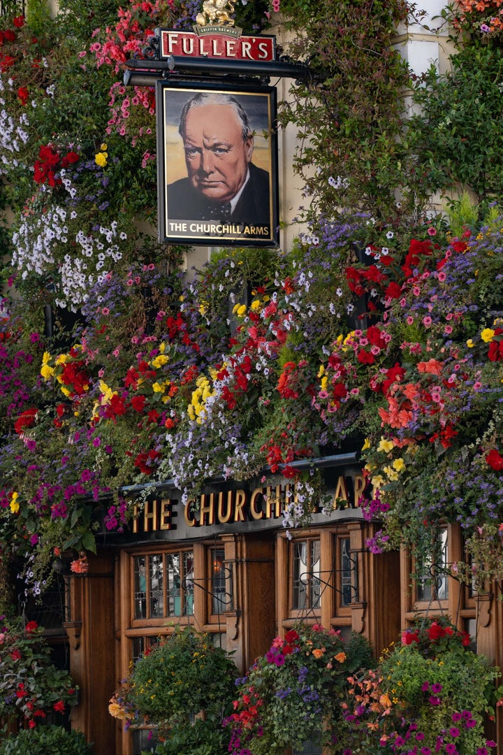 exterior of The Churchill Arms pub full of flowers