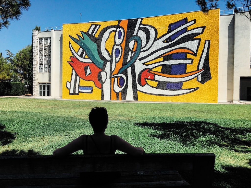 a woman sitting on a bench in front of the modernist exterior of the Musée Fernand Léger