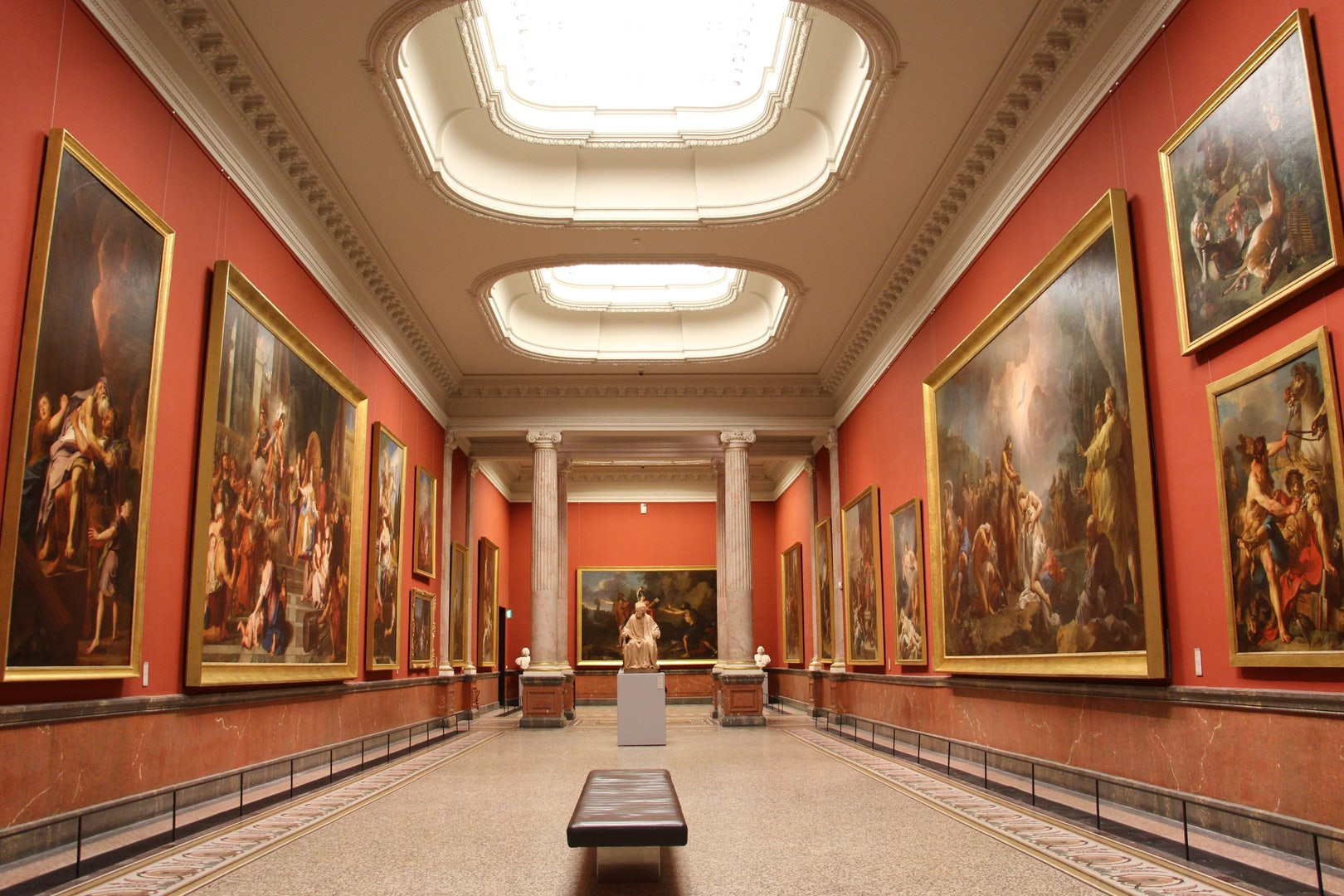 interior of the Musée de Fabre, paintings hanging at an orange pink wall