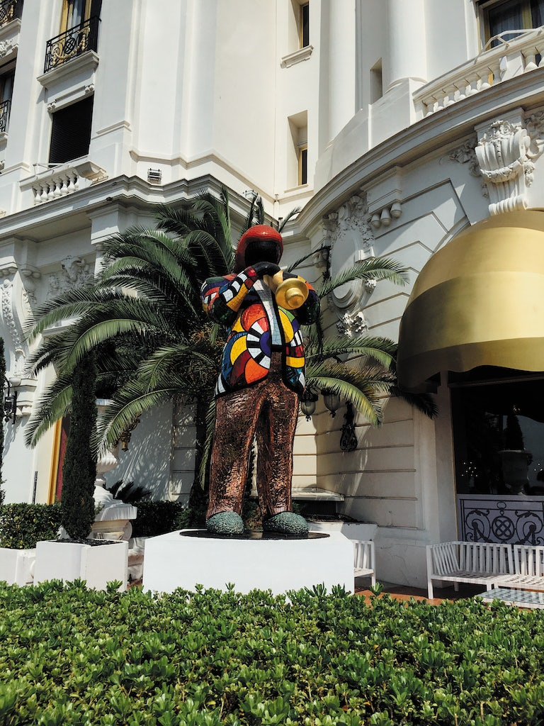 a colourful statue of a musician in front of Le Negresco hotel in Nice, France