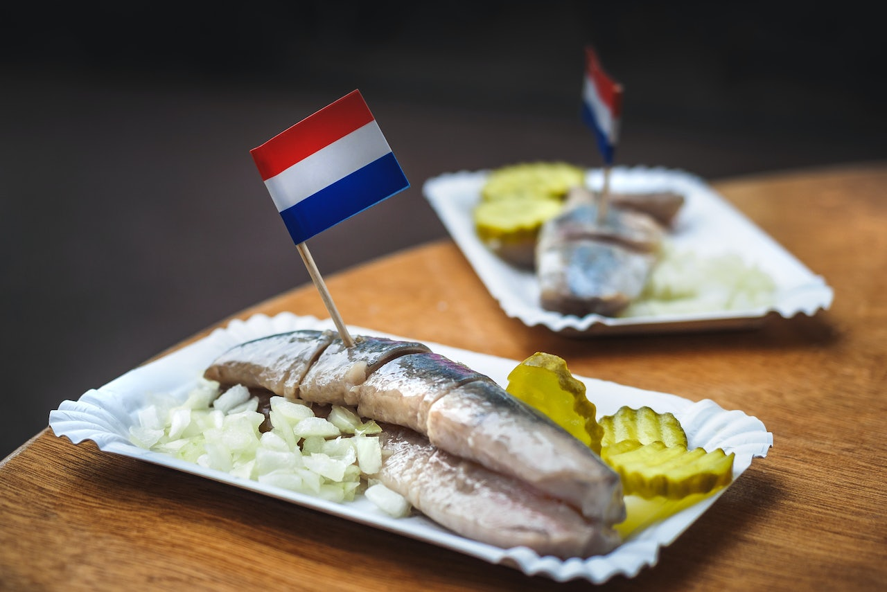 a plate of traditional Dutch-style hering with pickles and onion and a small Dutch flag