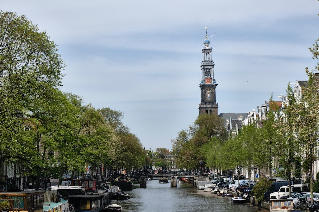 a view over the canal with the Westertoren in the background in Amsterdam